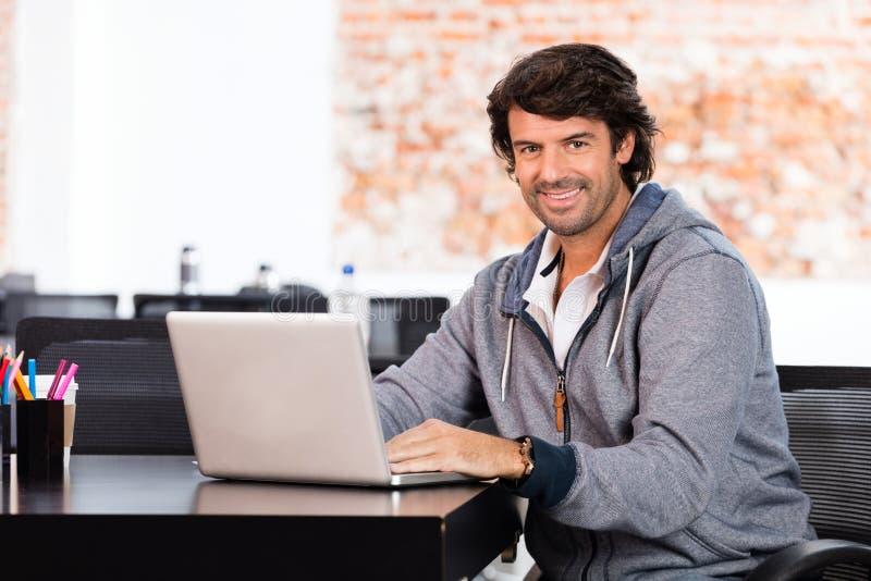 Mens die laptop toevallige zakenmanglimlach gebruiken stock foto