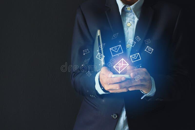 Mens die laptop voor het controleren van e-mail met pictogram of hologram op donkere achtergrond met behulp van stock fotografie