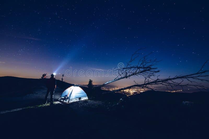 Mens die licht van zijn flitslicht richten aan de hemel stock afbeelding