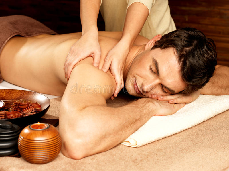 Mens die massage in de kuuroordsalon hebben stock afbeeldingen