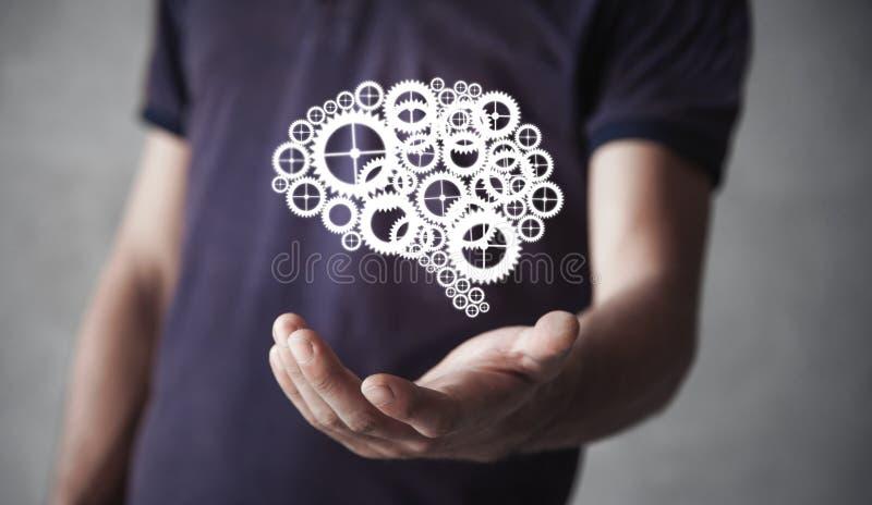 Mens die menselijke hersenen van toestellen en radertjesmechanisme houden stock afbeeldingen