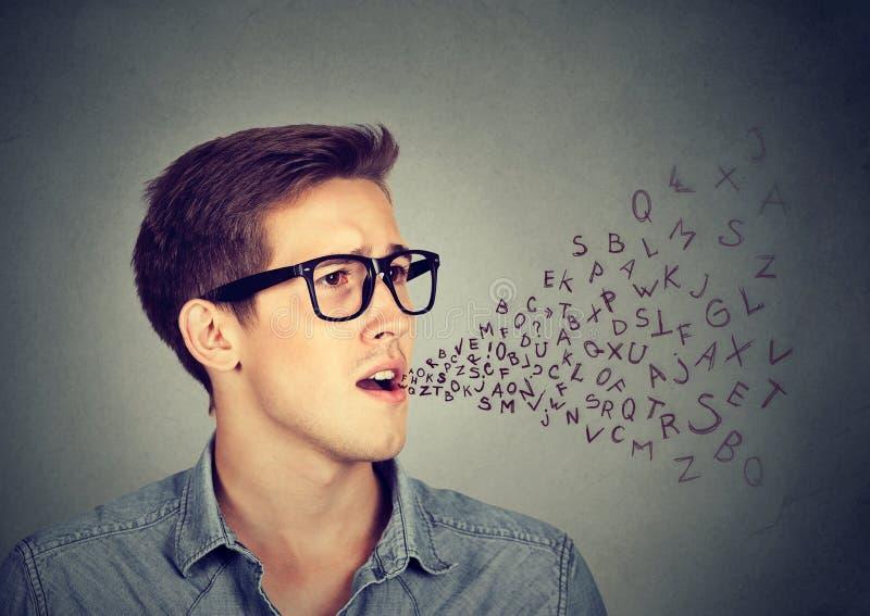 Mens die met alfabetbrieven spreken die uit zijn mond komen stock afbeeldingen