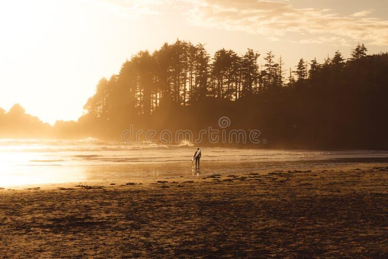 Mens die met branding op het strand met bos lopen erachter terwijl zonsondergang royalty-vrije stock foto's