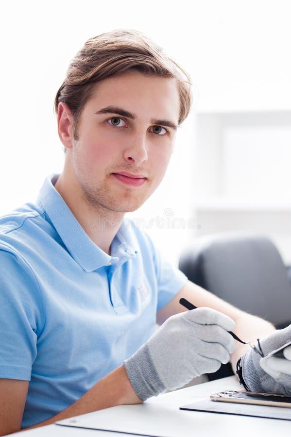 Mens die met computers en elektronika werken stock fotografie