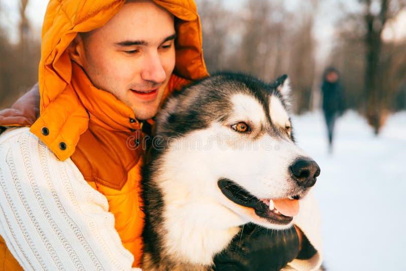 Mens die met de tijd van de hondwinter met sneeuw in de bosvriendschap van Malamute lopen en Huskies- stock foto