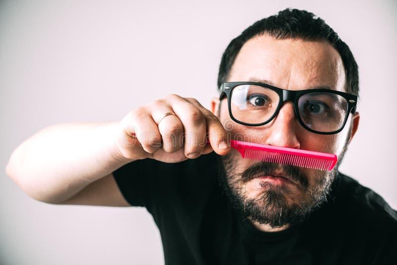 Mens die met glazen zijn baard met een roze kam kamt stock afbeeldingen