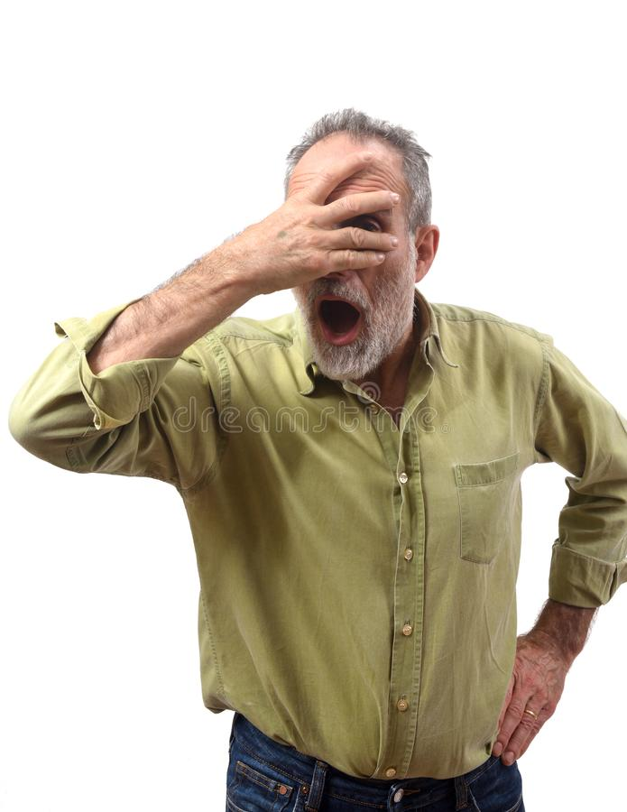 Mens die met hand op gezicht op witte achtergrond gluren stock fotografie