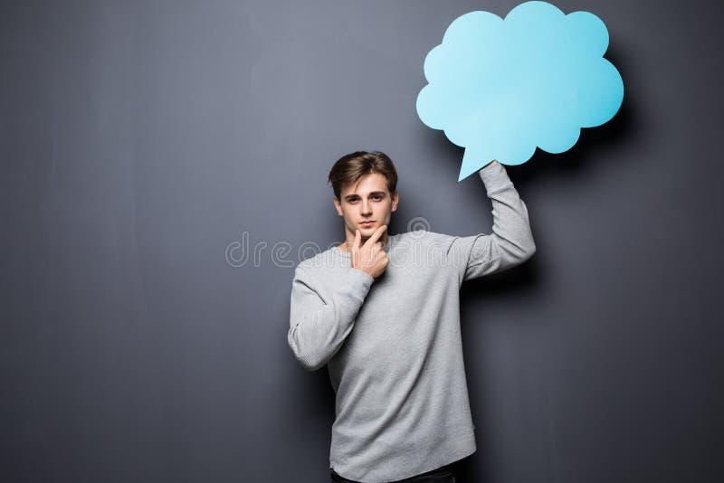 Mens die met handen op kin blauwe lege toespraakbel met ruimte voor tekst op grijze achtergrond houden stock afbeeldingen