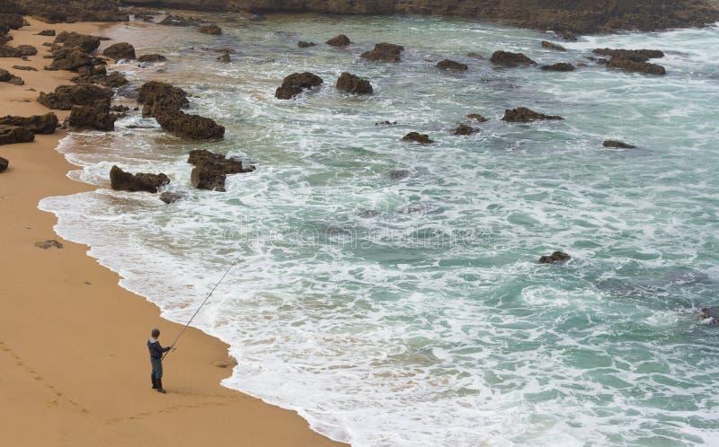 Mens die met hengel op het overzeese strand vissen stock foto's