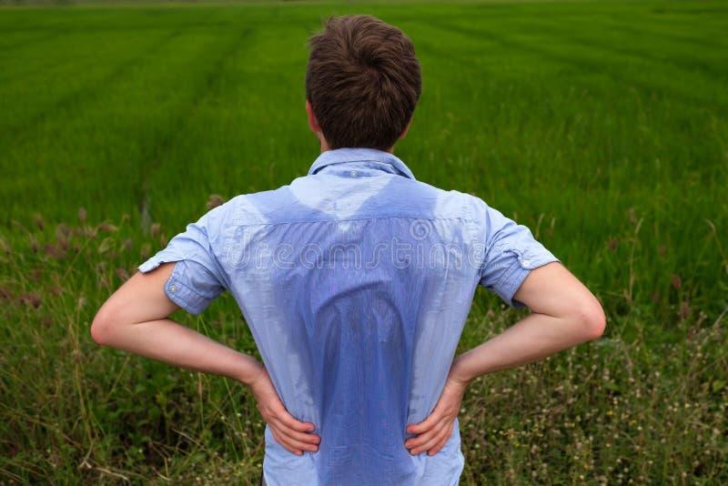 Mens die met hyperhidrosis zeer slecht onder oksel in blauw overhemd, op grijs zweten royalty-vrije stock foto's