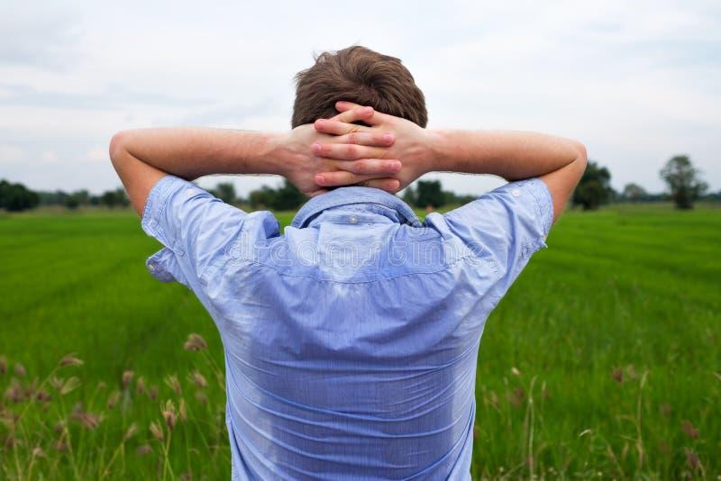 Mens die met hyperhidrosis zeer slecht onder oksel in blauw overhemd, op grijs zweten royalty-vrije stock afbeeldingen