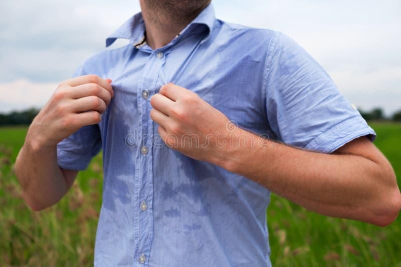 Mens die met hyperhidrosis zeer slecht onder oksel in blauw overhemd, op grijs zweten stock afbeelding