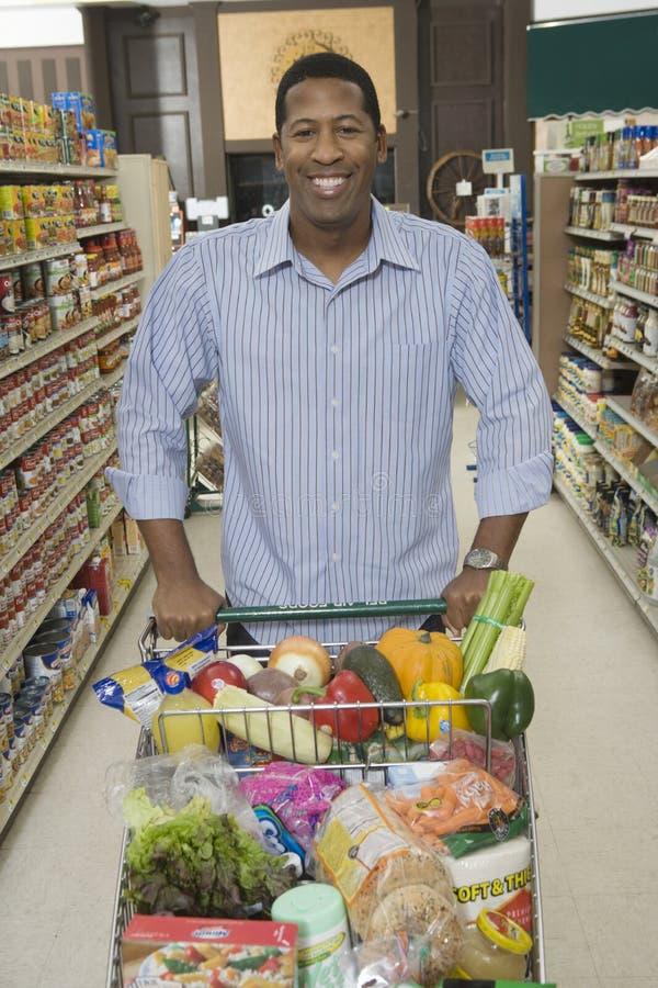 Mens die met Kruidenierswinkel in Supermarktdoorgang winkelen royalty-vrije stock foto's