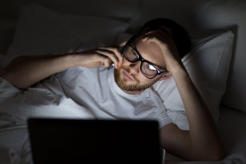 Mens die met laptop smartphone uitnodigen bij nacht stock foto