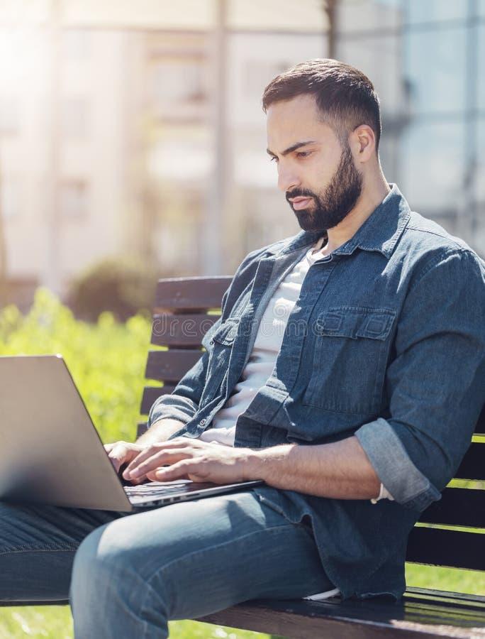 Mens die met laptop werkt royalty-vrije stock afbeelding