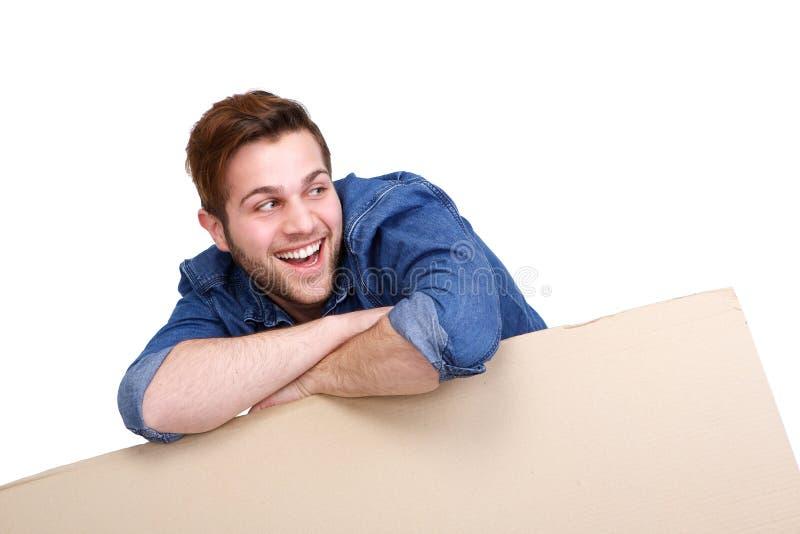 Mens die met leeg kartonteken glimlachen royalty-vrije stock foto