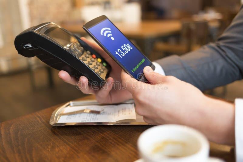 Mens die met NFC-technologie op mobiele telefoon, in restaurant betalen royalty-vrije stock afbeeldingen