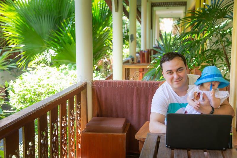 Mens die met notitieboekje in reis werken Met zuigeling op handen Het werk en babyzorg royalty-vrije stock foto's