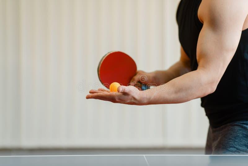Mens die met pingpongracket een bal voorbereidingen treffen te raken stock afbeelding