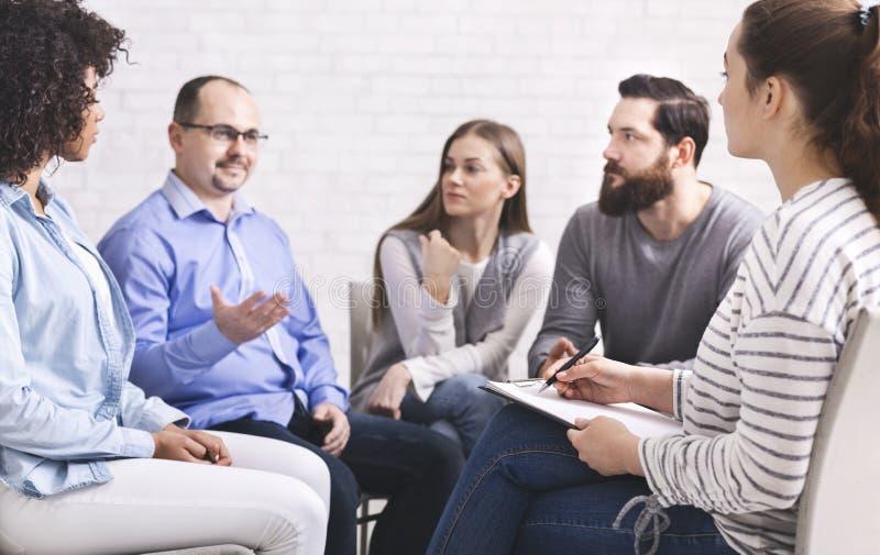 Mens die met psyhiatrist op de vergadering van de rehabgroep spreken stock afbeelding