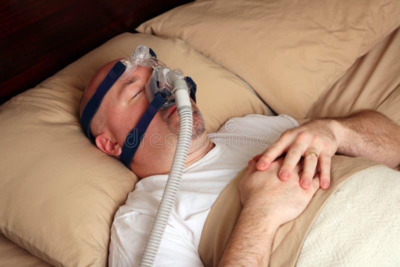 Mens die met slaapapnea een machine CPAP met behulp van stock foto