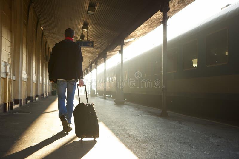 Mens die met zak bij station reizen stock afbeeldingen
