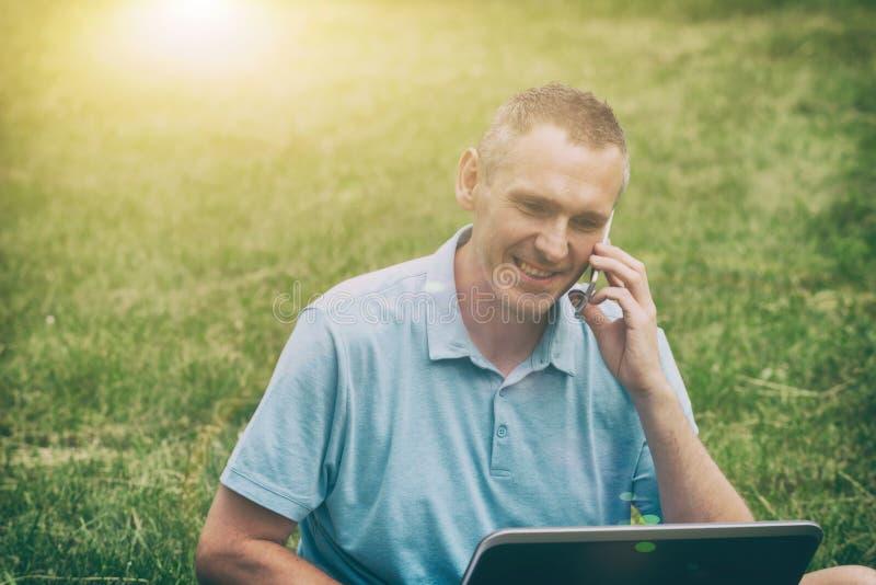 Mens die met zijn laptop in het park werken royalty-vrije stock afbeelding