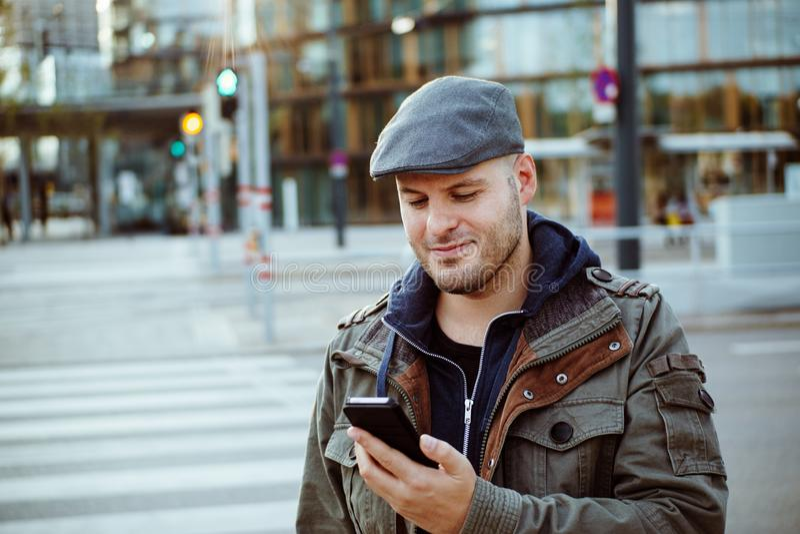 Mens die met zijn mobiele telefoon in zijn stedelijk leven communiceren Communicatie, technologie en levensstijlconcept stock foto's