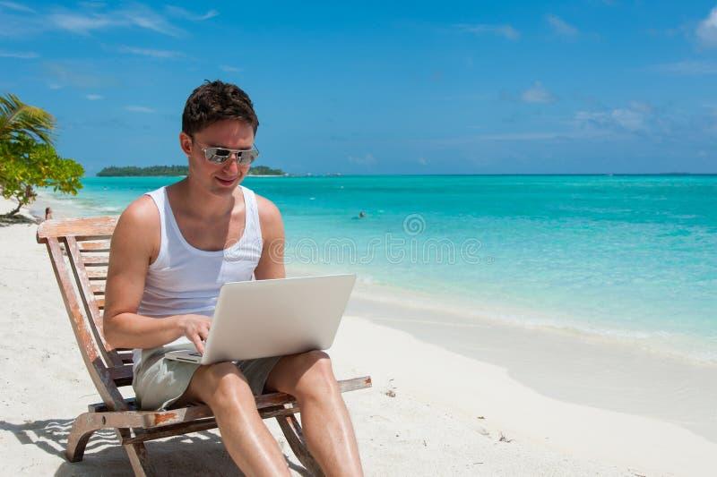 Mens die met zonnebril bij het strand met laptop ontspannen royalty-vrije stock fotografie