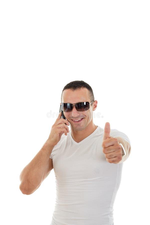 Mens die met Zonnebril in witte t-shirt Slimme Telefoon en s beantwoorden stock afbeeldingen