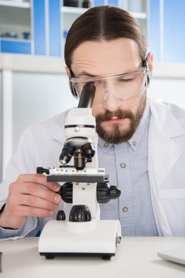 Mens die in microscoop kijken royalty-vrije stock fotografie