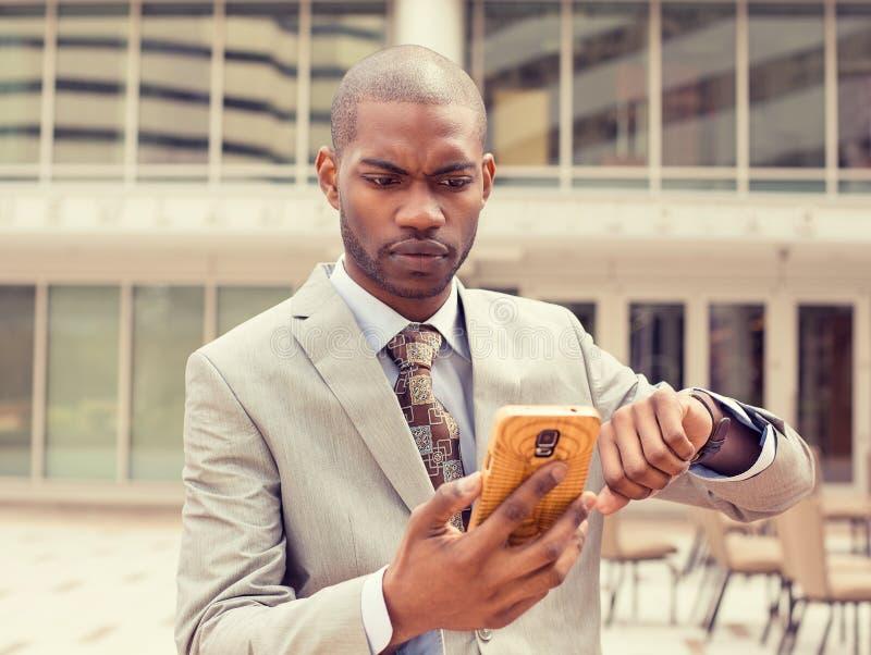 Mens die mobiel telefoonhorloge bekijken die uit van tijd lopen stock afbeeldingen