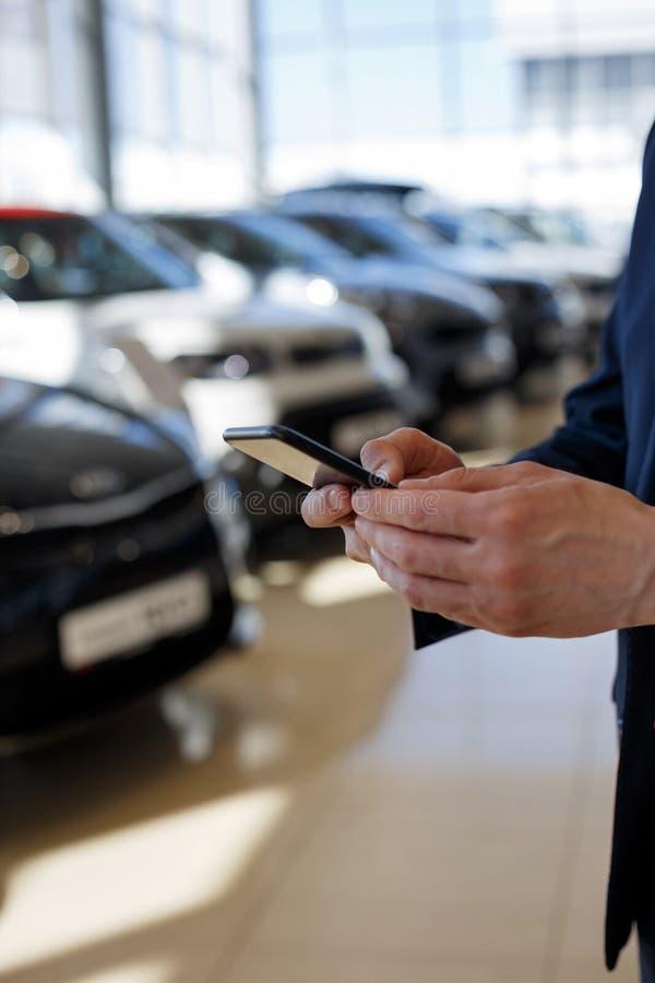 Mens die mobiele smartphone voor mededeling gebruiken bij handelaarstoonzaal stock afbeeldingen