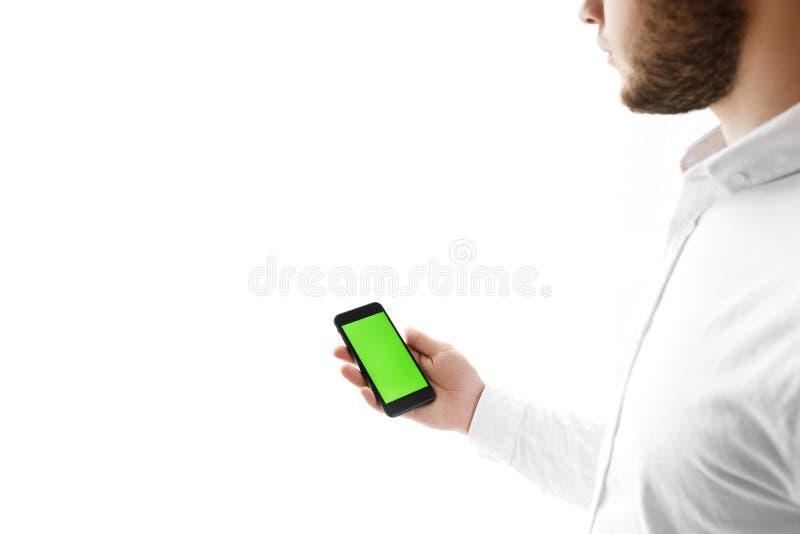 Mens die mobiele telefoon met behulp van terwijl status dichtbij venster Twee in: 1 royalty-vrije stock afbeeldingen