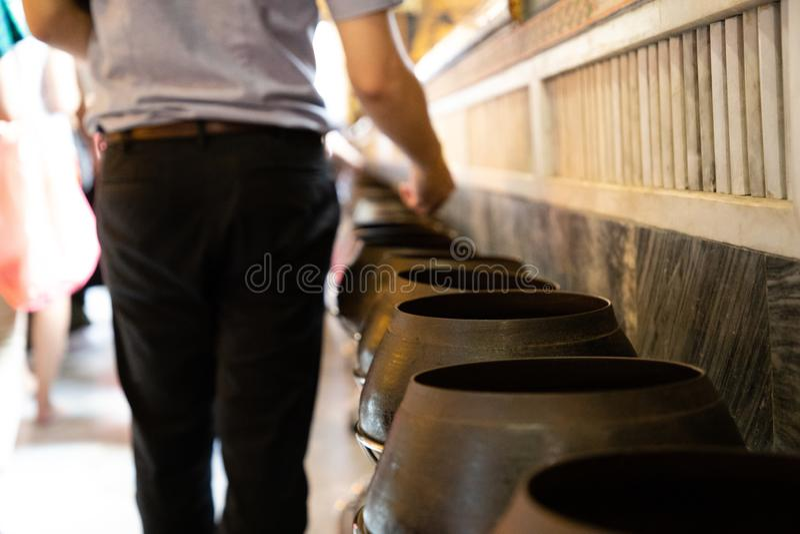 Mens die muntstukken in Thaise tempel voor geluk en welvaart schenken stock foto's