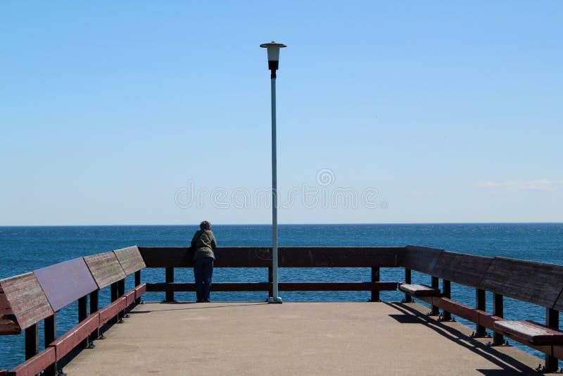 Mens die naast Enige Lantaarn aan het eind van een landend stadium op een duidelijke blauwe hemel leunen stock foto