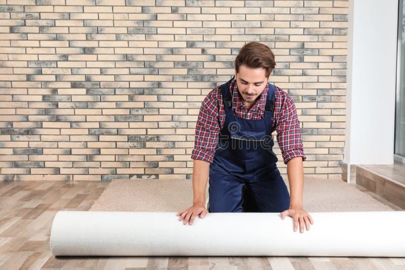 Mens die nieuwe tapijtbevloering ontwikkelen royalty-vrije stock fotografie