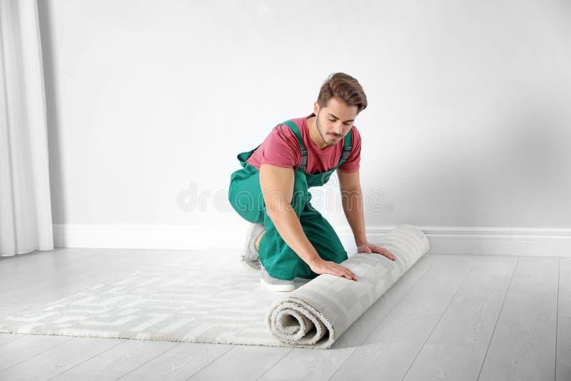 Mens die nieuwe tapijtbevloering ontwikkelen royalty-vrije stock afbeelding