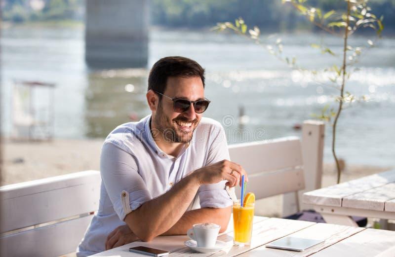 Mens die ochtend van koffie op rivierstrand genieten royalty-vrije stock afbeelding
