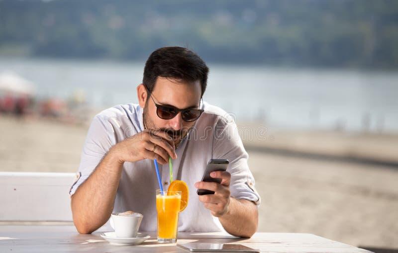 Mens die ochtend van koffie op rivierstrand genieten royalty-vrije stock afbeeldingen