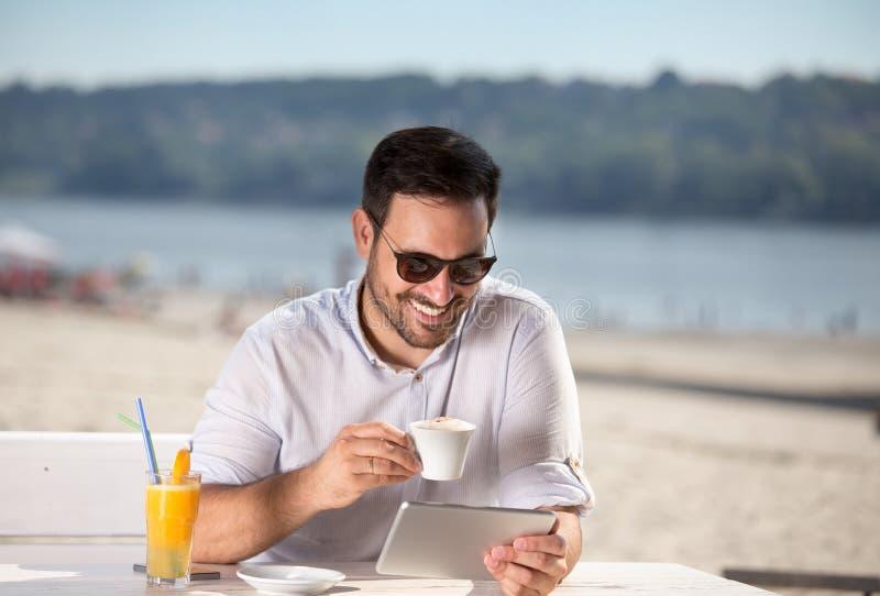 Mens die ochtend van koffie op rivierstrand genieten royalty-vrije stock fotografie