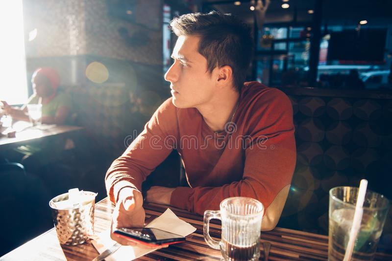 Mens die ochtendontbijt met koffie in diner koffie hebben en zijn mobiele telefoon met behulp van stock fotografie