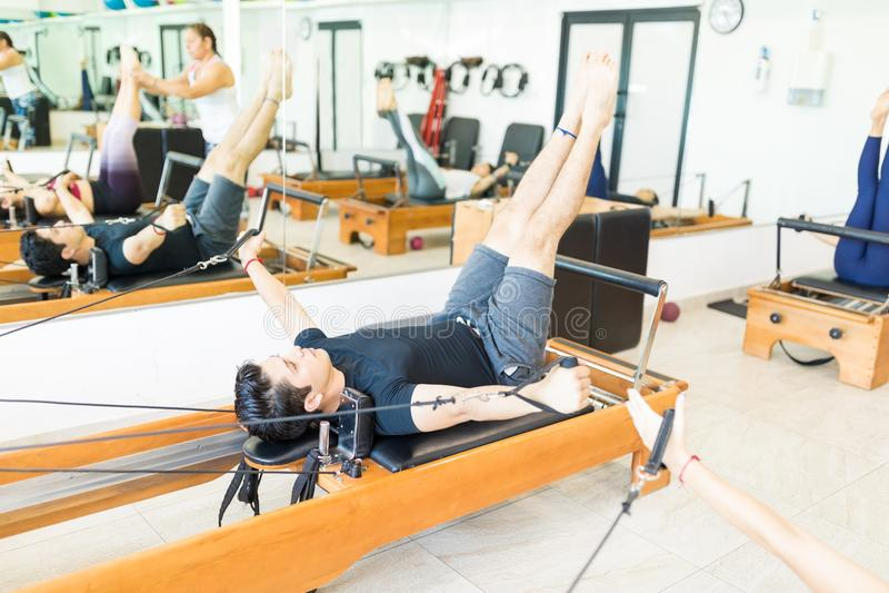 Mens die Oefening op Pilates-Hervormer in Gezondheidsclub doen stock afbeeldingen