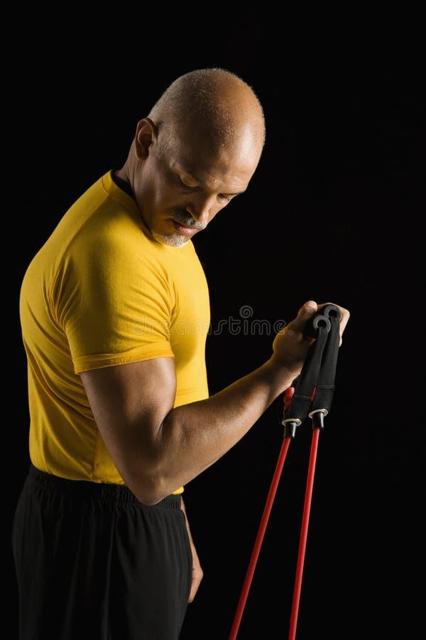 Mens die oefeningsapparatuur met behulp van. stock fotografie