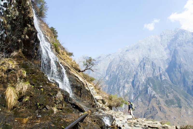 Mens die omhoog Berghellingswaterval bekijken stock foto