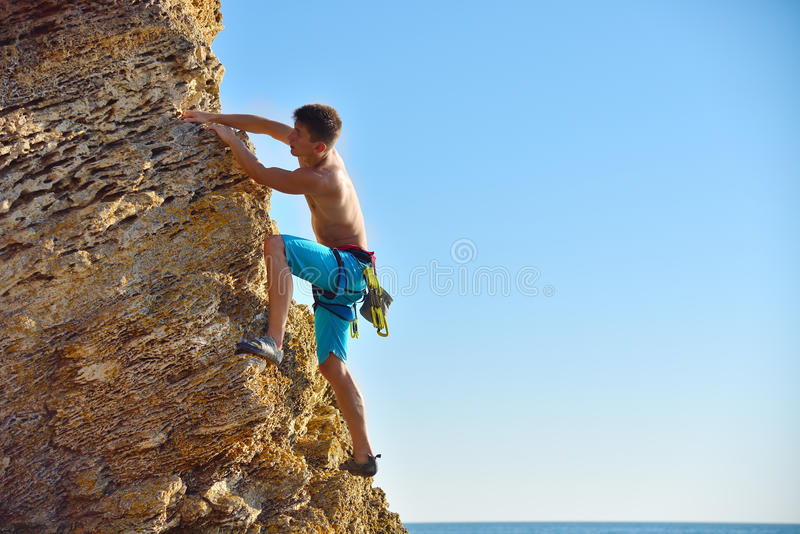 Mens die omhoog op berg beklimt stock afbeeldingen