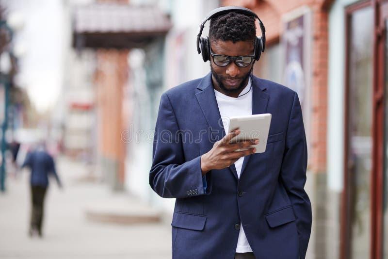 Mens die onderaan de straat met gadgets lopen stock foto