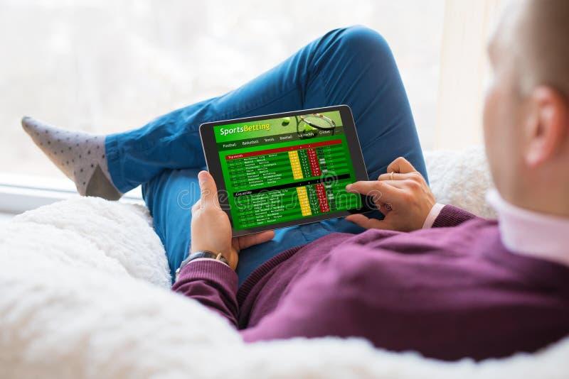 Mens die online sporten gebruiken die de dienst wedden op tablet stock foto