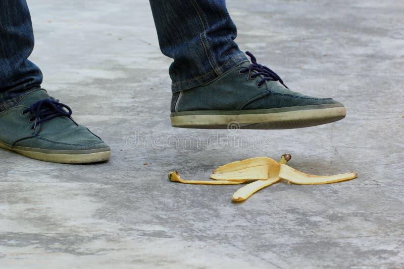 Mens die op bananeschil of schil, ongevallenconcept stappen stock fotografie