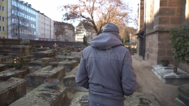 Mens die op begraafplaats, het bezoeken graf lopen die van gehouden van relatief, pijn van verlies voelen royalty-vrije stock foto
